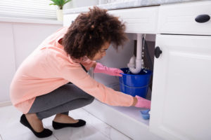 woman in pink shirt looking under sink